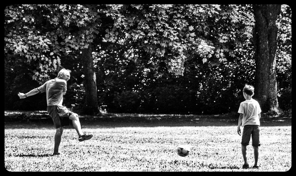 Father-kicking-soccer-ball-to-son